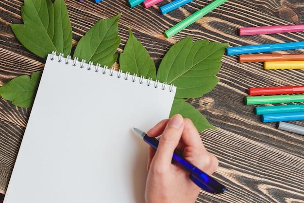 木製のテーブルに空白のノートブックで素敵な女性の手書き