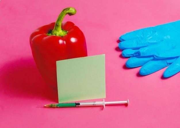注射器、ステッカー、青い手袋、ピンクの背景の赤唐辛子、