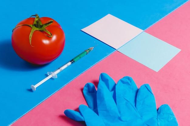 注射器、ステッカー、青い手袋、ピンクと青の背景に赤いトマト、