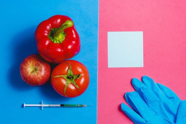 注、注射器の緑の液体、赤いトマト、リンゴ、コショウ、青い手袋。