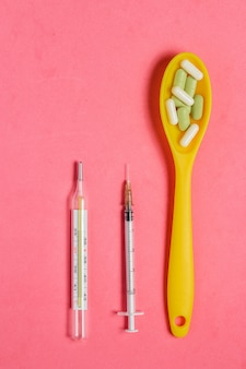 ピンクの背景に黄色のスプーン、注射器、温度計の丸薬とカプセルの品揃え。