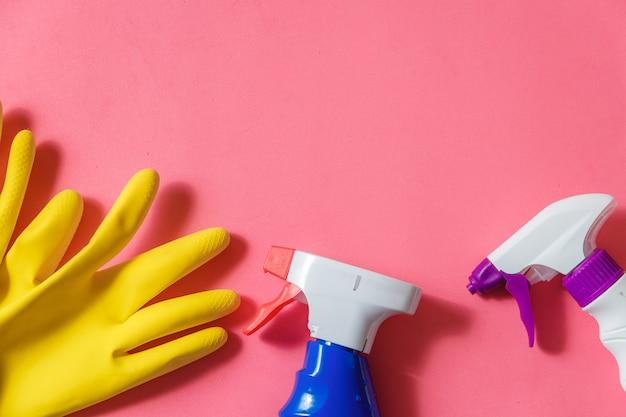 クリーニング製品。ホームクリーニングの概念。ピンクの背景。タイポグラフィとロゴ。コピースペース。平干し。上面図。
