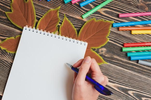 Славно женская рука, пишущая в пустой тетради на деревянном столе