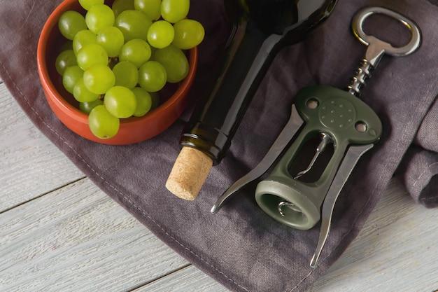 ワインのボトル、グラス、コルク抜き、テーブルの上のブドウ。上面図。