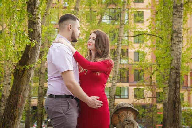 Счастливая молодая пара ожидает ребенка в парке летом