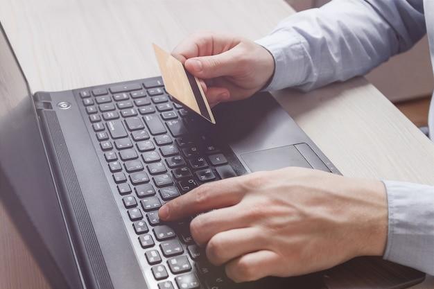 男の手がクレジットカードを保持しているとラップトップを使用しています。オンラインショッピング