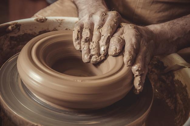 陶器のホイールを使用して鍋を作る老人