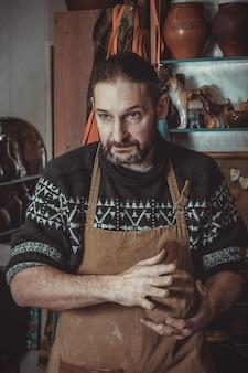 粘土を粉砕する成人男性の陶工マスター