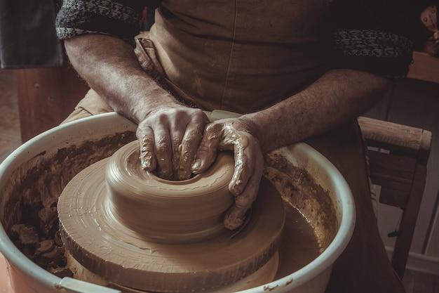 スタジオで陶器の車輪を使用してポットを作る老人。閉じる。