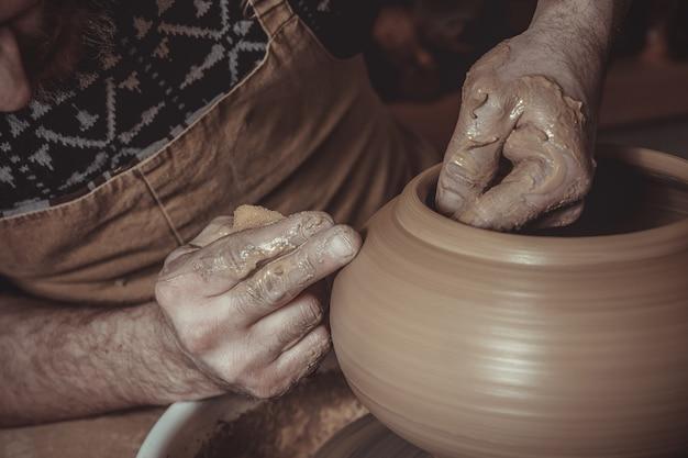 老人男性のスタジオで陶器のホイールを使用して鍋を作る