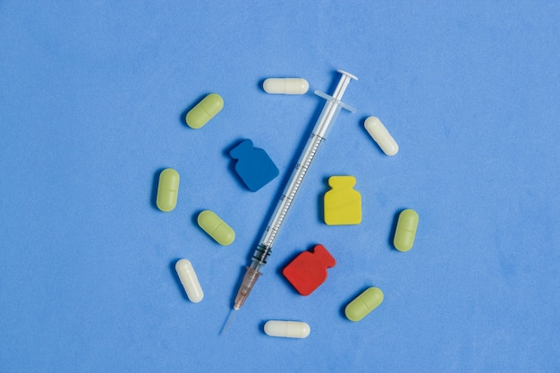 Набор различных таблеток, капсул, шприц на синем. медицина креативная концепция.
