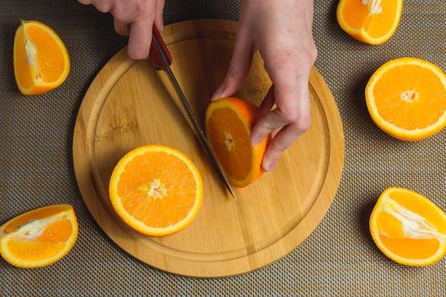 女性の手は木製のまな板にナイフでオレンジをスライスします。フルーツ健康的なコンセプトです。上面図。