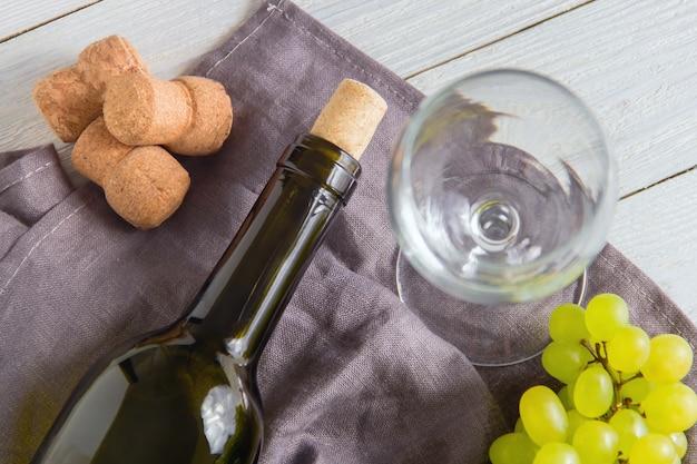 白い木製のテーブルのブドウとワインの瓶