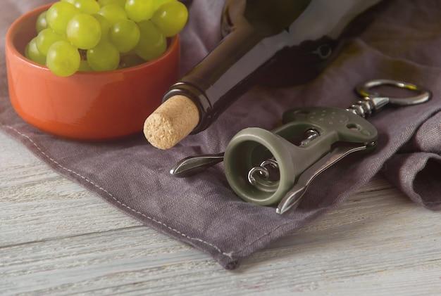 ワインの瓶、グラス、コルク抜き、テーブルの上のブドウ