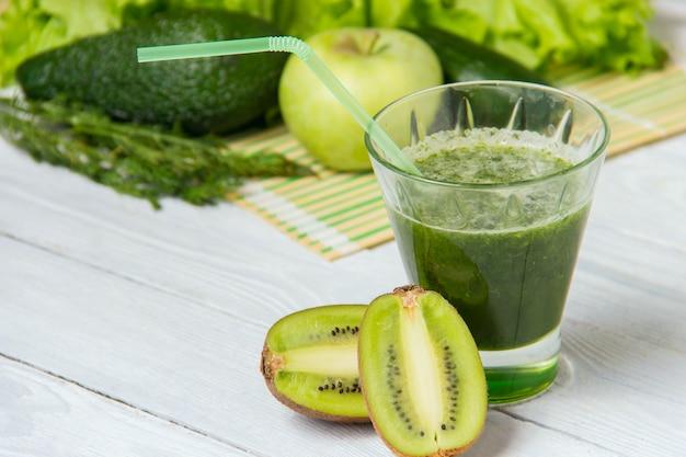 Здоровый зеленый коктейль с ингредиентами на белом фоне деревянные