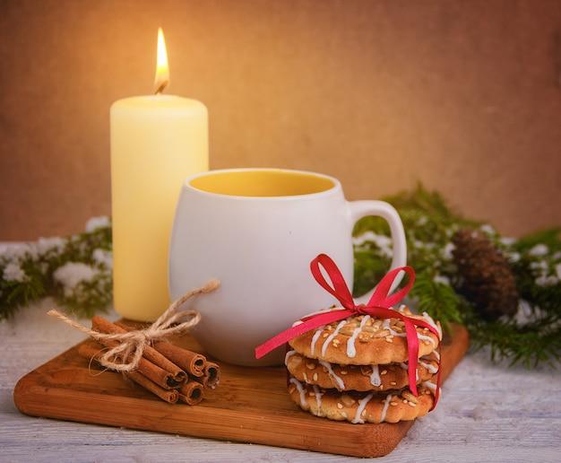 木製のテーブルにお茶のカップとクリスマスクッキー。クリスマスの飾り。