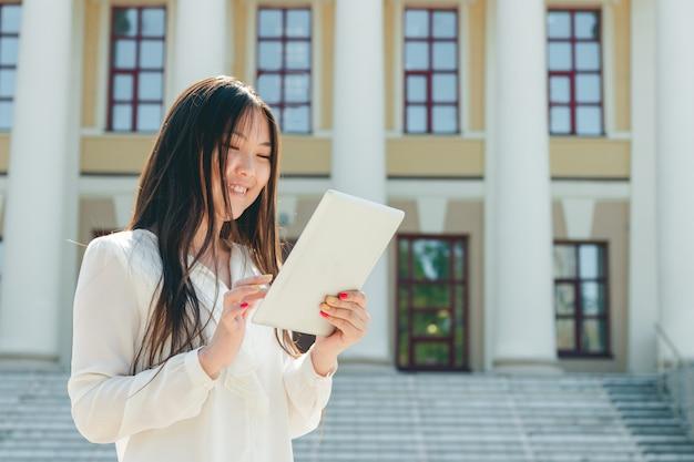 タブレットコンピューターを使用して美しい若いアジア女性