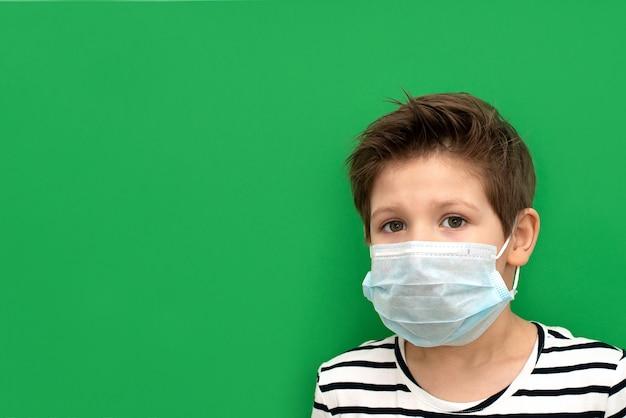 コロノウイルス中に分離された医療用マスクを着ている少年。