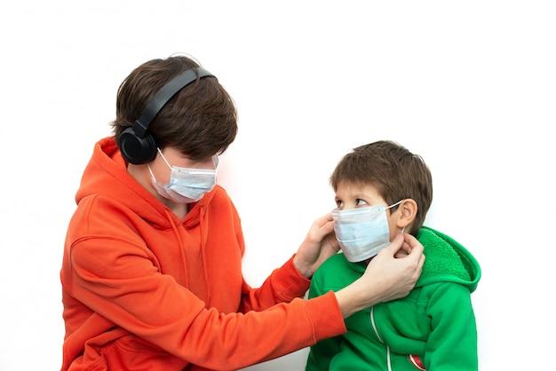 明るい服で医療マスクをかぶる子供たち。コロナウイルス防止
