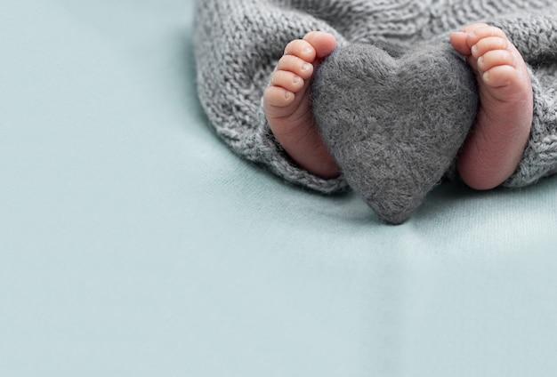 羊毛の心、優しさを持つ生まれたばかりの赤ちゃんの足。コピースペース、愛、家族の概念