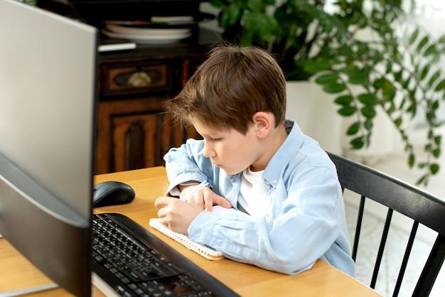 Дистанционное обучение во время изоляции во время карантина на короновирус. мальчик и ноутбук у себя дома. стиль жизни