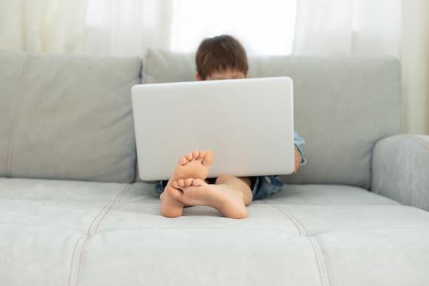 Дети и гаджеты. дистанционное обучение во время изоляции во время карантина. мальчик и ноутбук у себя дома. стиль жизни.