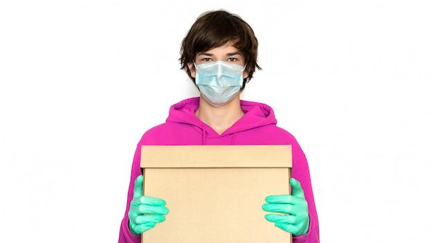 Бесконтактная доставка. мужчина в медицинской маске и перчатках держит коробку. изолировать копию пространства.