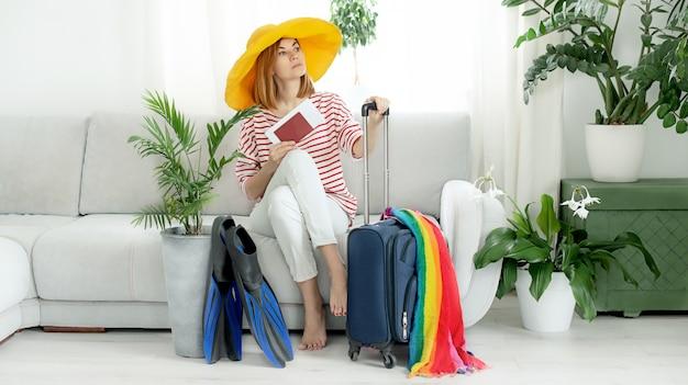 Красивая девушка в желтой шляпе сидит дома и планирует поездку в отпуск. чемодан и ласты для дайвинга.