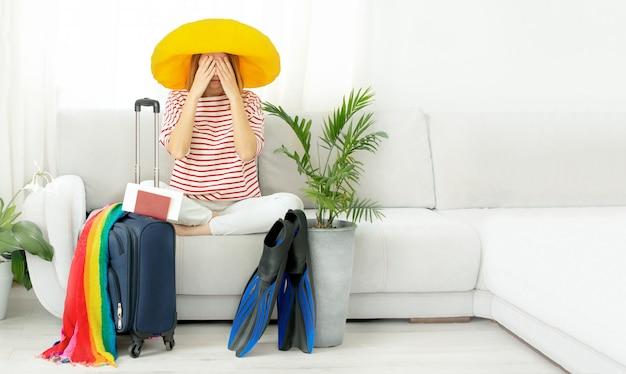 Расстроенная плачущая девушка без лица в желтой шляпе сидит дома и планирует поездку в отпуск. чемодан и ласты для дайвинга.