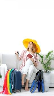 Красивая девушка в желтой шляпе сидит дома и планирует поездку в отпуск. ласты для дайвинга. в ожидании путешествия.