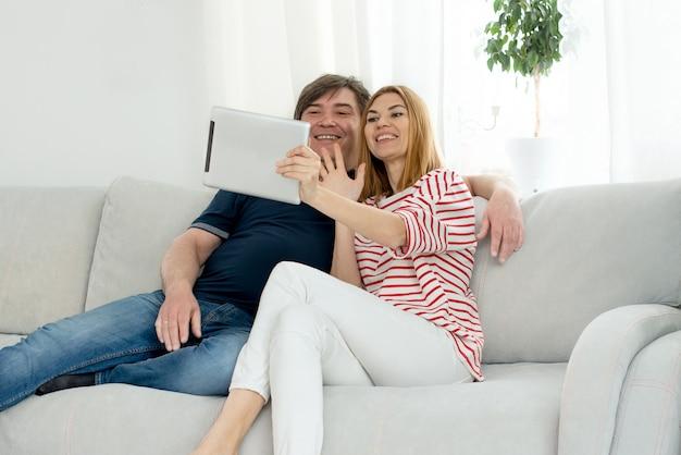 Мужчина и женщина общаются по видеосвязи. общаться в чате и махать на экране компьютера.