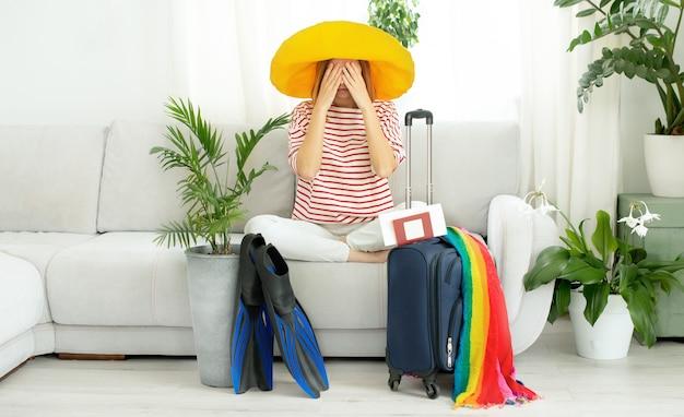 До неузнаваемости расстроенная девушка в желтой шапке сидит дома и планирует поездку в отпуск. в ожидании путешествия.