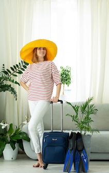Красивая девушка в желтой шляпе сидит дома и планирует поездку в отпуск. чемодан и ласты для дайвинга. в ожидании путешествия. закрытие границ и запрет на полеты