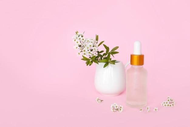 オイル入りガラスのコスメティックボトル。ターコイズブルーの壁に小さな白い花を持つ女性のための製品のコンテナー。化粧品の瓶。テキストのための場所
