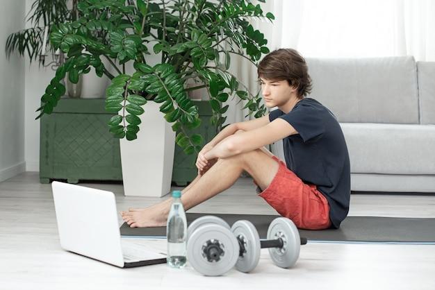 ハンサムな若い男は自宅でオンラインスポーツをします。ティーンエイジャーは部屋でトレーニング