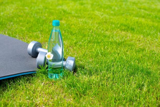 Бутылка с водой, гантелями и ковриком для занятий спортом и йогой на зеленой траве. копировать пространство