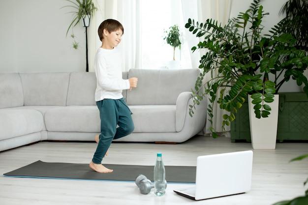 少年は自宅でオンラインでスポーツに出かけます。子供は部屋で運動をします。