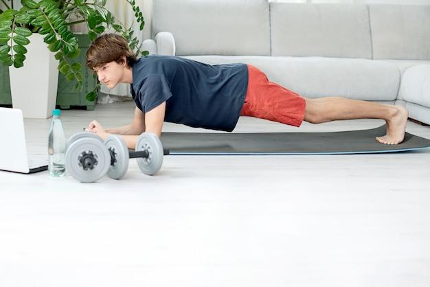 若い男性がオンラインで自宅でスポーツに出かける