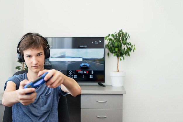 Подросток играет в компьютерную игру с наушниками и джойстиком, игровой приставкой.