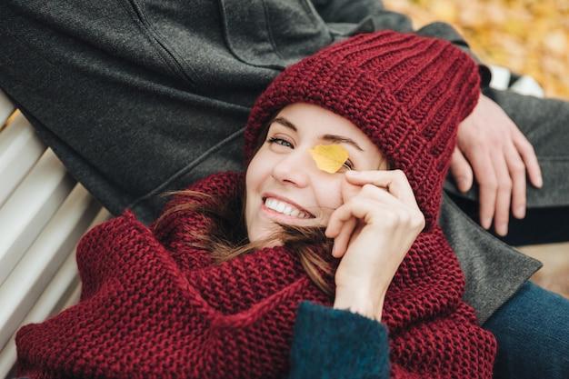 Приятно выглядящая самка закрывает глаза, прикрывает глаза листом, лежит на руках парня. хорошее настроение