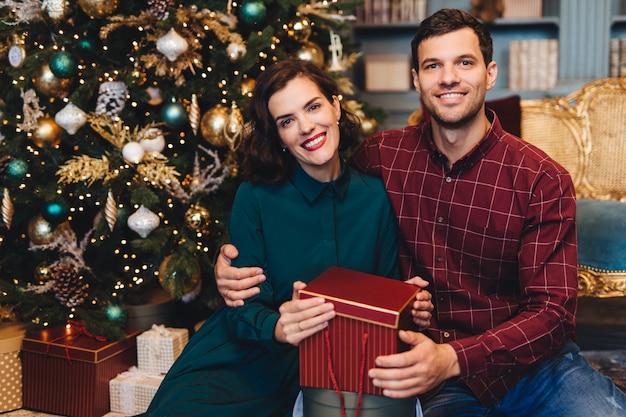 Счастливая восхитительная влюбленная пара, обнимаются, сидят возле украшенной новогодней елки, держат подарок