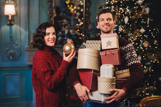 Улыбающаяся женщина носит красный вязаный свитер, держит стеклянный шар, как украшает елку, стоит возле мужа, который держит груды подарков