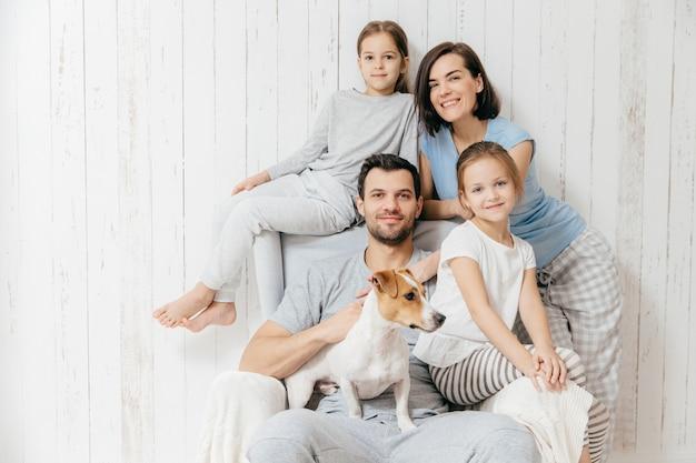 Счастливые родители с двумя дочерьми и собакой позируют на белом фоне