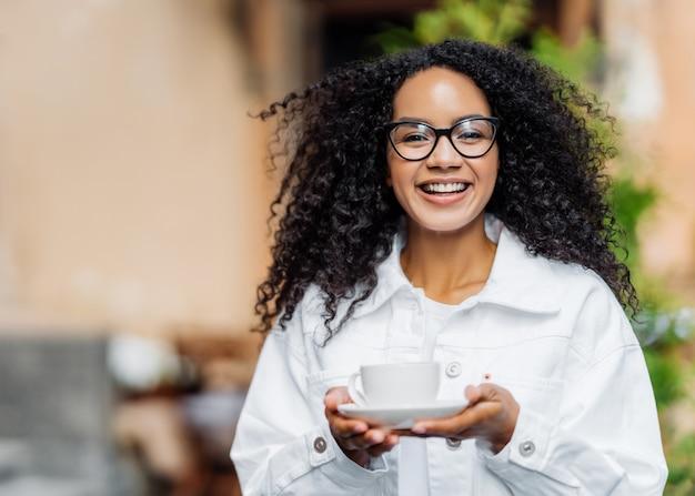 ぱりっとした髪の幸せな黒い肌の女性、白いジャケットを着て、熱いお茶を飲んで、通りを歩いている