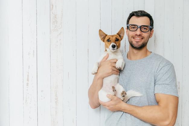 Счастливый небритый кобель носит повседневную одежду, держит щенка,