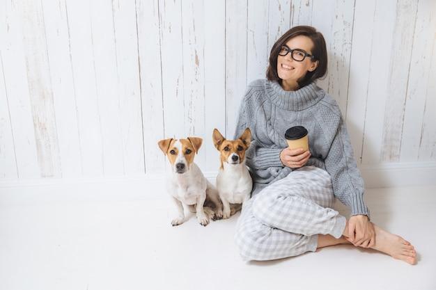 Улыбающаяся веселая молодая самка носит теплый шерстяной свитер, квадратные очки, пьет горячий напиток