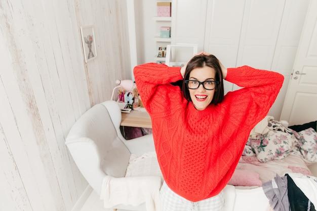 Вид сверху голубоглазой, брюнетки-молодой женщины в повседневном красном свитере, носит прямоугольные очки, стоит в своей просторной комнате дома