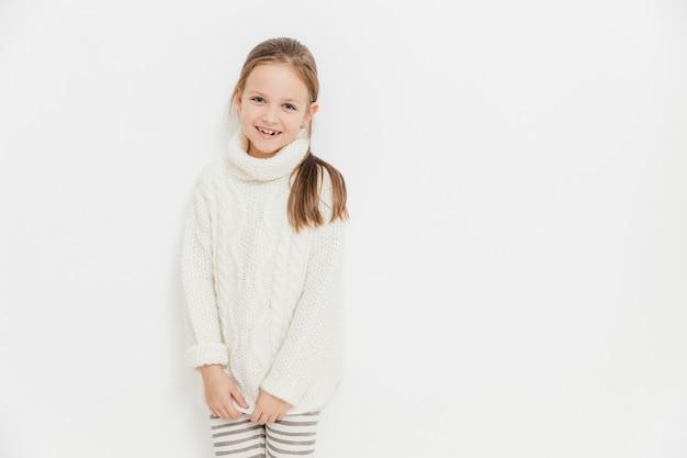 喜んで満足している女の子は暖かい白いニットのセーターを着て、うれしそうな表情を持ち、スタジオに立っています