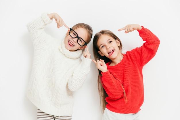 暖かいニットセーターで幸せな小さな女性の子供、顔をしかめるし、面白い表現を持っています。