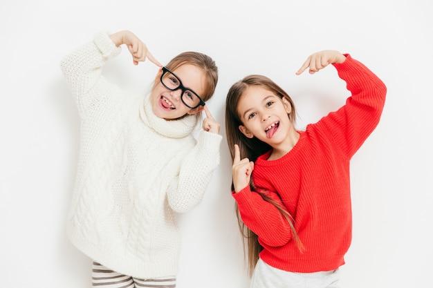 気分が良いうれしそうな女の子、特大のセーターと眼鏡を着用し、クールなサインを作り、白に対して一緒にポーズをとる